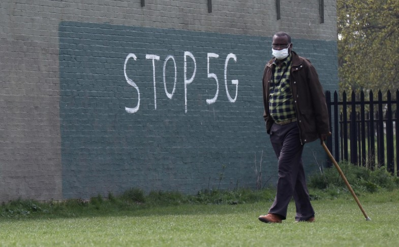 """A man wearing a face mask during an outbreak of coronavirus disease (COVID-19) walks past a graffiti that reads """"STOP 5G"""" in London"""